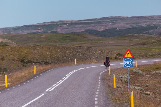 Młoda dziewczyna na rowerze po utwardzonej drodze w islandii.