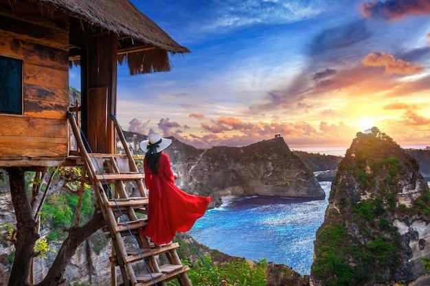 Młoda dziewczyna na schodach domu na drzewie o wschodzie słońca na wyspie nusa penida, bali w indonezji