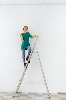 Młoda dziewczyna na schodach maluje wałkiem białą ścianę. naprawa wnętrza.