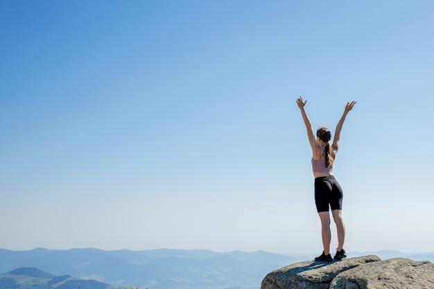 Młoda dziewczyna na szczycie góry podniosła ręce do błękitnego nieba. kobieta wspięła się na szczyt i cieszyła się swoim sukcesem. widok z tyłu.