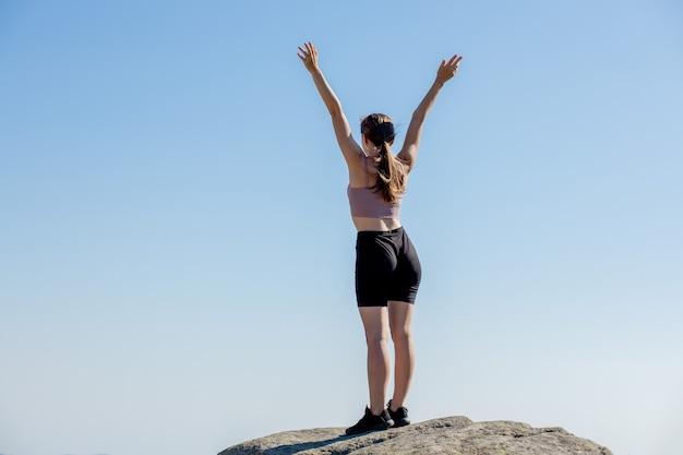Młoda dziewczyna na szczycie góry podniosła ręce do błękitnego nieba. kobieta wspięła się na szczyt i cieszyła się swoim sukcesem.