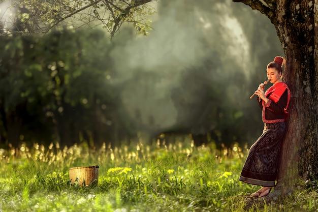 Młoda dziewczyna na tajlandzkich tradycyjnych ubraniach bawić się instrument drzewem