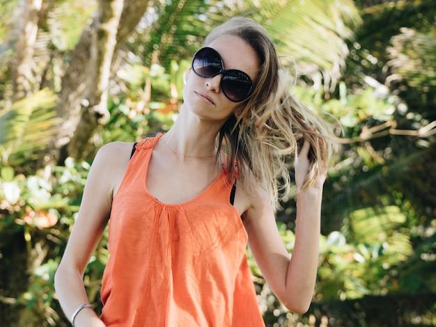 Młoda dziewczyna na wakacjach w pomarańczowej kamizelce i okularach przeciwsłonecznych na tropikalnej wyspie. wiejący silny wiatr z oceanu