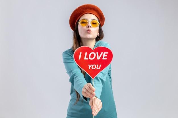 Młoda dziewczyna na walentynki w kapeluszu z okularami trzymając czerwone serce na patyku z tekstem kocham cię w aparacie pokazując gest pocałunek na białym tle