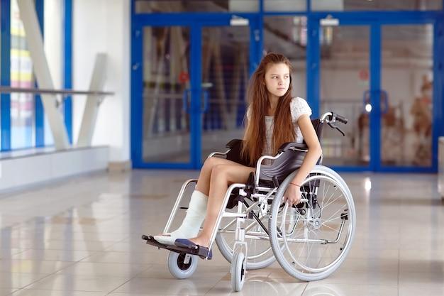 Młoda dziewczyna na wózku inwalidzkim stoi na korytarzu szpitala.