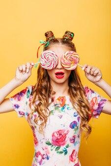 Młoda dziewczyna na żółtych słodyczach gospodarstwa