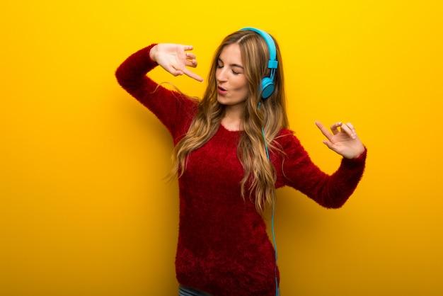 Młoda dziewczyna na żywy żółty słuchanie muzyki w słuchawkach i taniec