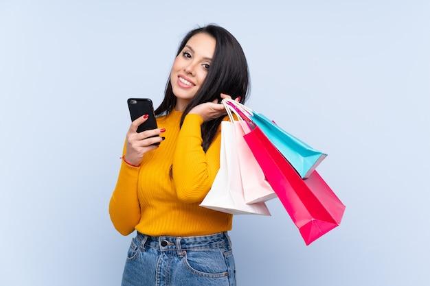 Młoda dziewczyna nad błękitnymi mień torba na zakupy i telefonem komórkowym