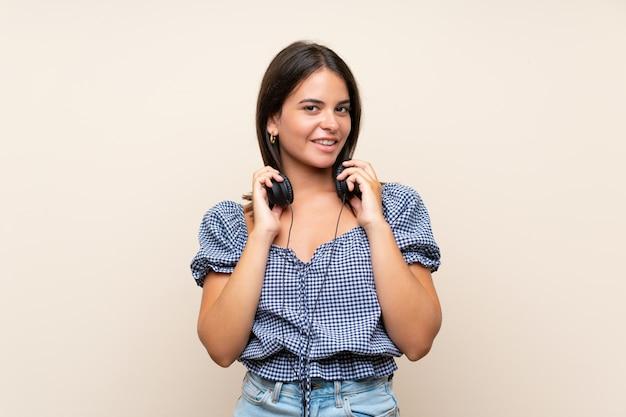 Młoda dziewczyna nad odosobnioną ścianą słucha muzyka z hełmofonami