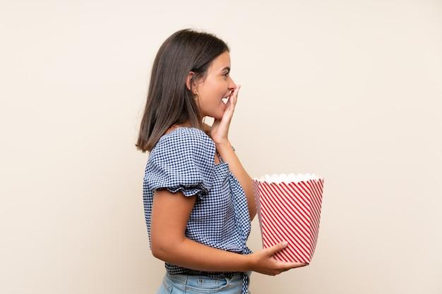 Młoda dziewczyna nad odosobnioną ścianą trzyma puchar popkorny