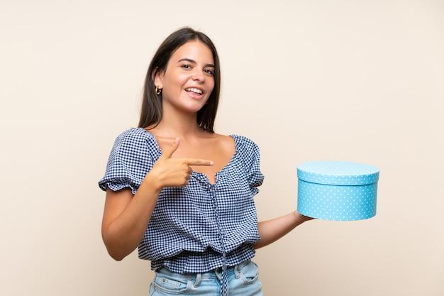 Młoda dziewczyna nad odosobnionym ściennym mienie prezenta pudełkiem