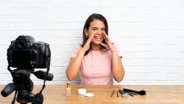 Młoda dziewczyna nagrywa samouczek wideo krzyczący z szeroko otwartymi ustami