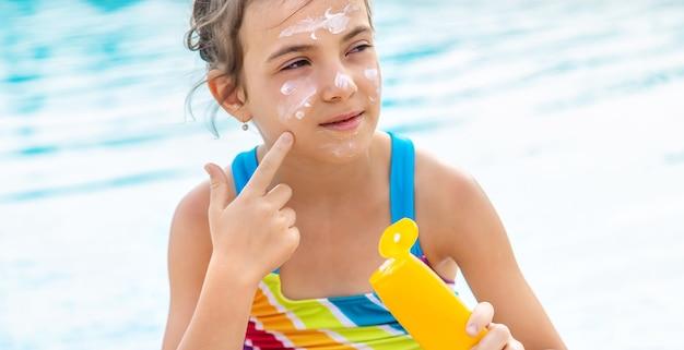 Młoda dziewczyna nakłada krem przeciwsłoneczny na twarz przy basenie