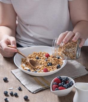 Młoda dziewczyna nalewa musli do białego talerza na śniadanie z jagodami przy brązowym drewnianym stole. wegańskie jedzenie