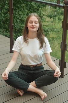 Młoda dziewczyna, nastolatka ager siedzi pozycji lotosu, medytacji