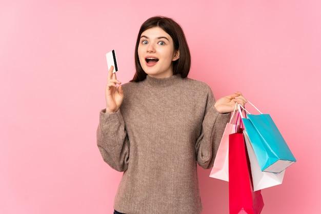 Młoda dziewczyna nastolatka na różowym ścianie trzymając torby na zakupy i zaskoczony