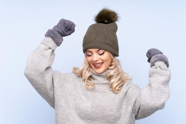 Młoda dziewczyna nastolatka z zimowym kapeluszu świętuje zwycięstwo