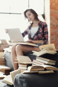 Młoda dziewczyna nastolatka za pomocą komputera przenośnego otoczony wieloma książkami.