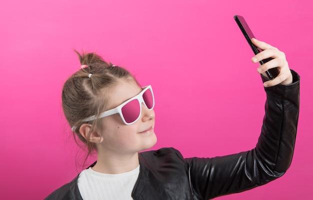 Młoda dziewczyna nosi czarną skórzaną kurtkę i robi zdjęcia telefonem komórkowym.