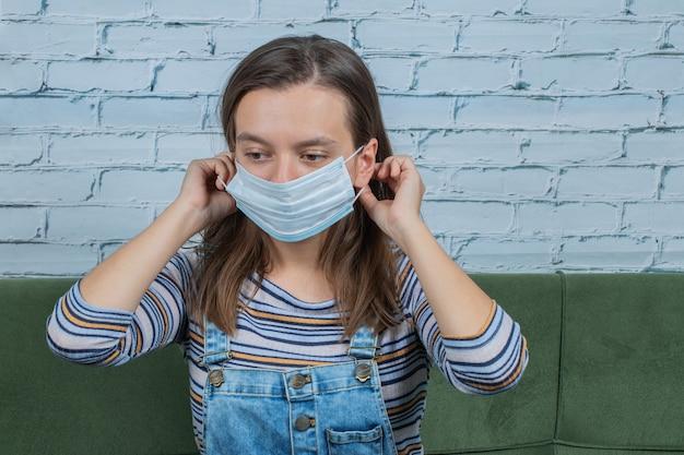 Młoda dziewczyna nosi maskę na twarz, aby zapobiec wirusowi covid