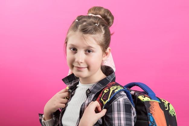 Młoda dziewczyna nosi tornister szkoły na białym tle na różowo