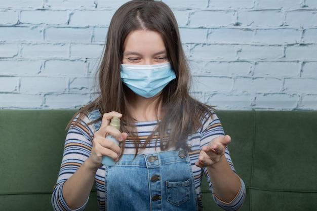 Młoda dziewczyna nosząca maskę na twarz i rozpylająca alkohol na dłonie