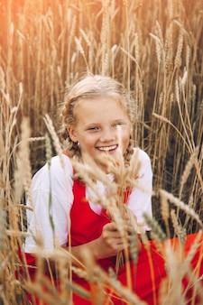 Młoda dziewczyna o blond włosach w polu pszenicy