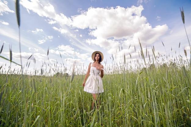Młoda dziewczyna o długich ciemnych włosach idzie na zielone pole z wysoką trawą z twarzą skierowaną do kamery w krótkiej białej sukience i słomkowym kapeluszu