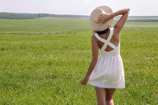 Młoda dziewczyna o długich ciemnych włosach stojących na zielonym polu z zieloną trawą plecami do aparatu w krótkiej białej letniej sukience i słomkowym kapeluszu. rozkłada ręce i cieszy się naturą.