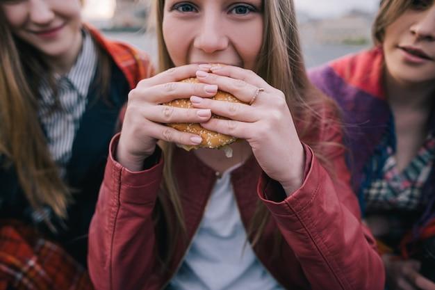 Młoda dziewczyna o gorących oczach zjada hamburgera, z bliska. spotkanie ze znajomymi z fast foodami na wynos. koncepcja przeżywienia i niepowodzenia diety, wahania nastroju w jedzeniu