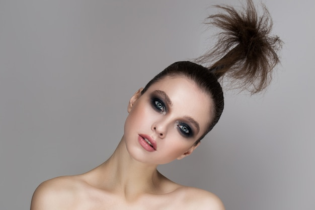 Młoda dziewczyna o jasnym makijażu i promiennej skórze.