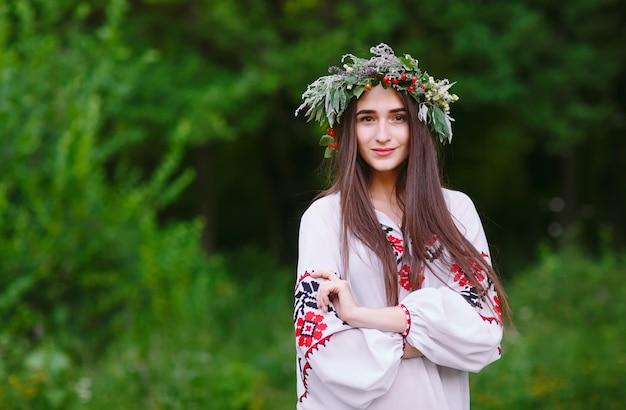 Młoda dziewczyna o słowiańskim wyglądzie z wieńcem z dzikich kwiatów w środku lata.