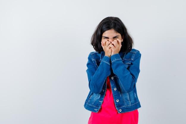 Młoda dziewczyna obejmujące usta rękami w czerwonej koszulce i dżinsowej kurtce i patrząc szczęśliwy.