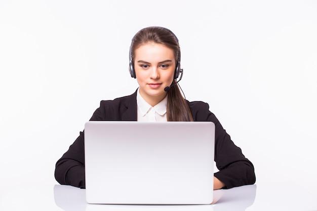 Młoda dziewczyna obsługi klienta z zestawem słuchawkowym w jej miejscu pracy na białym tle na białej ścianie