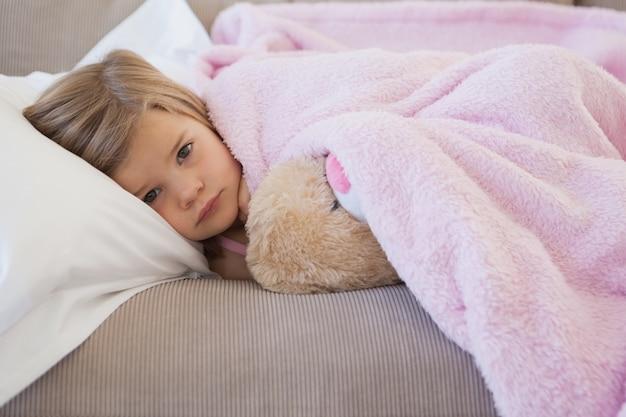 Młoda dziewczyna odpoczywa na kanapie z faszerującą zabawką