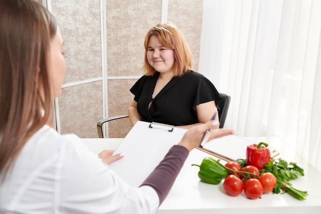 Młoda dziewczyna odwiedza dietetyka, aby schudnąć przy pomocy programu diety.