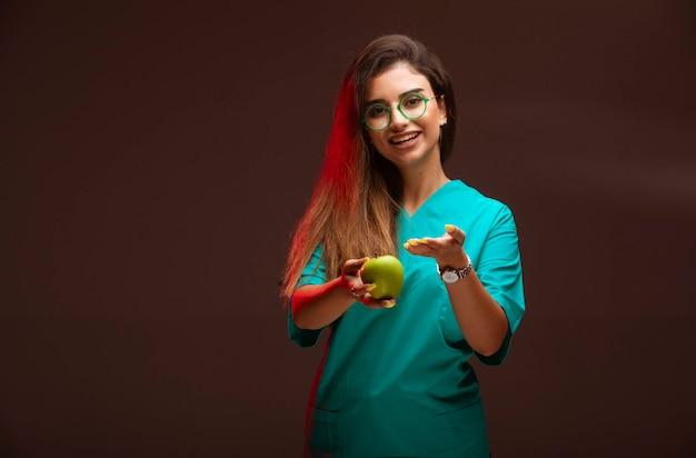 Młoda dziewczyna oferuje zielone jabłko w dłoni.