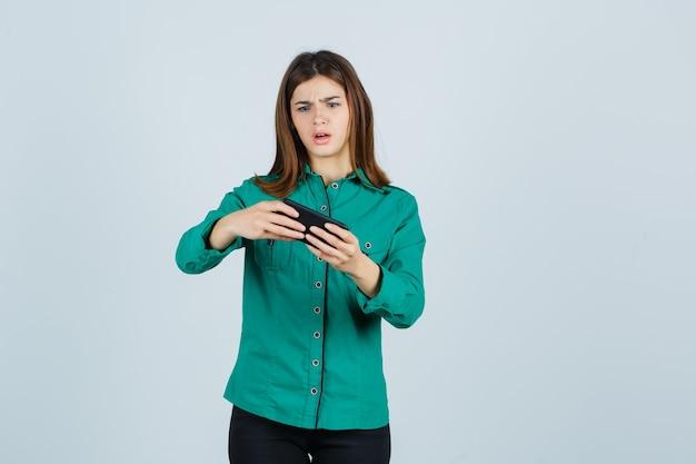 Młoda dziewczyna ogląda filmy na telefonie w zielonej bluzce, czarnych spodniach i wygląda na zszokowaną. przedni widok.