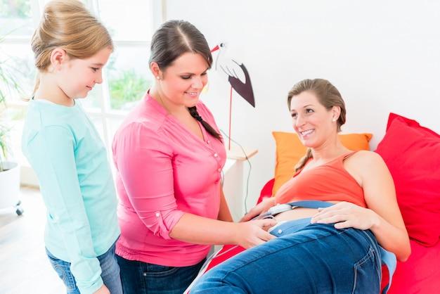 Młoda dziewczyna ogląda położnej przywiązując ctg do brzucha w ciąży m