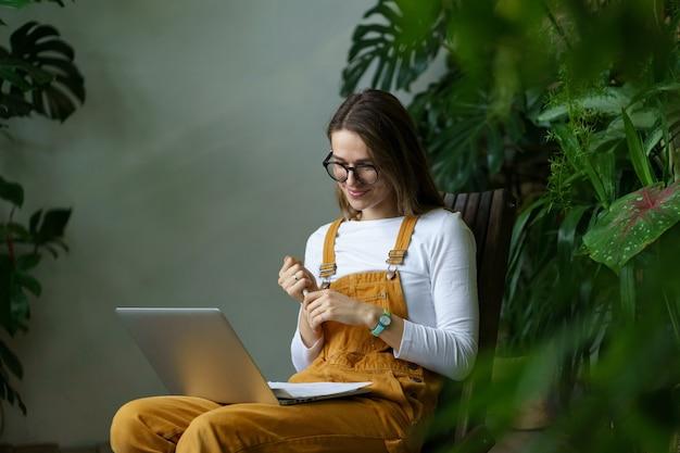 Młoda dziewczyna ogrodnik student ogląda seminarium internetowe na temat ogrodnictwa domowego kwiaciarnia pielęgnacja roślin domowych