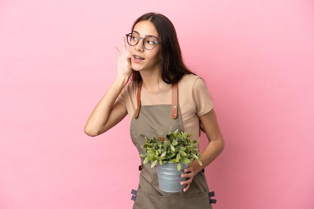 Młoda dziewczyna ogrodnik trzymając roślinę na białym tle na różowym tle, słuchając czegoś, kładąc rękę na uchu