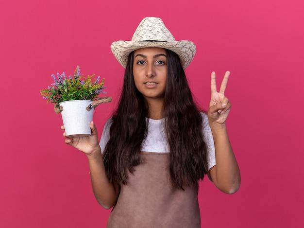 Młoda dziewczyna ogrodnik w fartuch i letni kapelusz gospodarstwa roślina doniczkowa uśmiechnięta pokazując znak v stojący nad różową ścianą