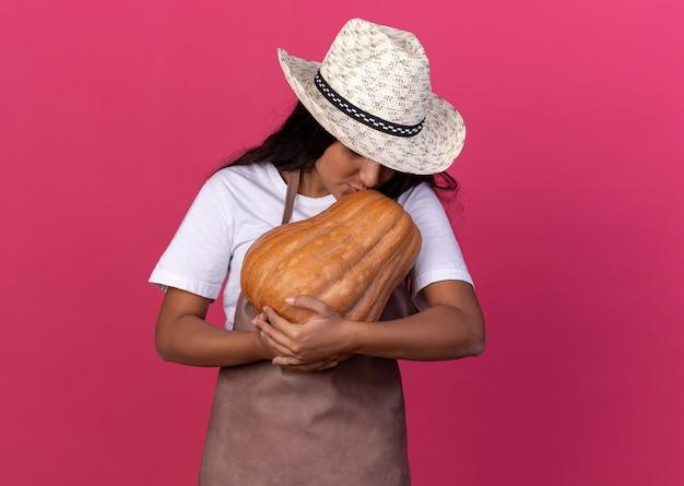 Młoda dziewczyna ogrodnik w fartuch i letni kapelusz trzymając dyni całuje go stojąc na różowej ścianie