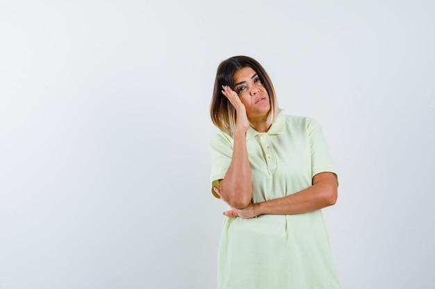 Młoda dziewczyna opierając policzek na dłoni, myśląc o czymś w koszulce i patrząc zamyślony. przedni widok.
