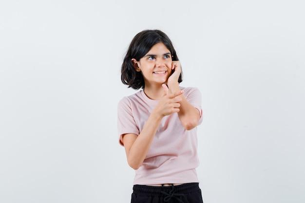 Młoda dziewczyna opierając policzek na dłoni w różowej koszulce i czarnych spodniach i wygląda na szczęśliwą