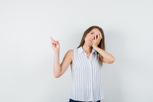Młoda dziewczyna opierając twarz na dłoni z palcem w t-shirt, dżinsy i patrząc zmęczony, widok z przodu.
