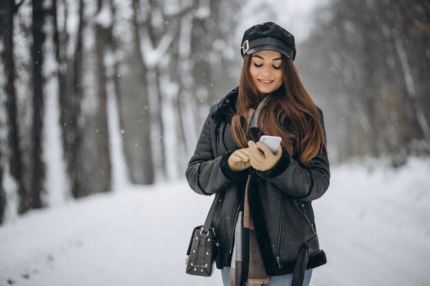 Młoda dziewczyna opowiada na telefonie w zima parku