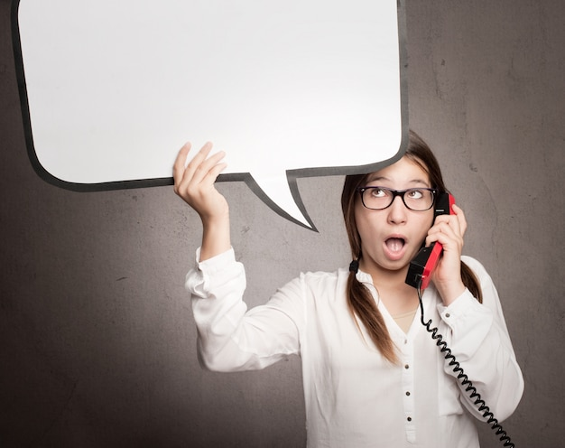 Młoda dziewczyna opowiada telefonicznie i trzyma mowa bąbel