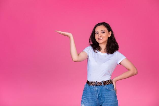 Młoda dziewczyna otwiera dłoń i coś przedstawia.