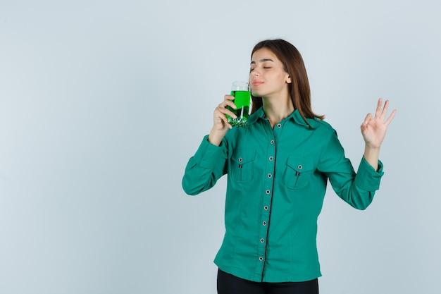 Młoda dziewczyna pachnąca szklanką zielonego płynu, pokazująca znak ok w zielonej bluzce, czarnych spodniach i wyglądająca optymistycznie, widok z przodu.
